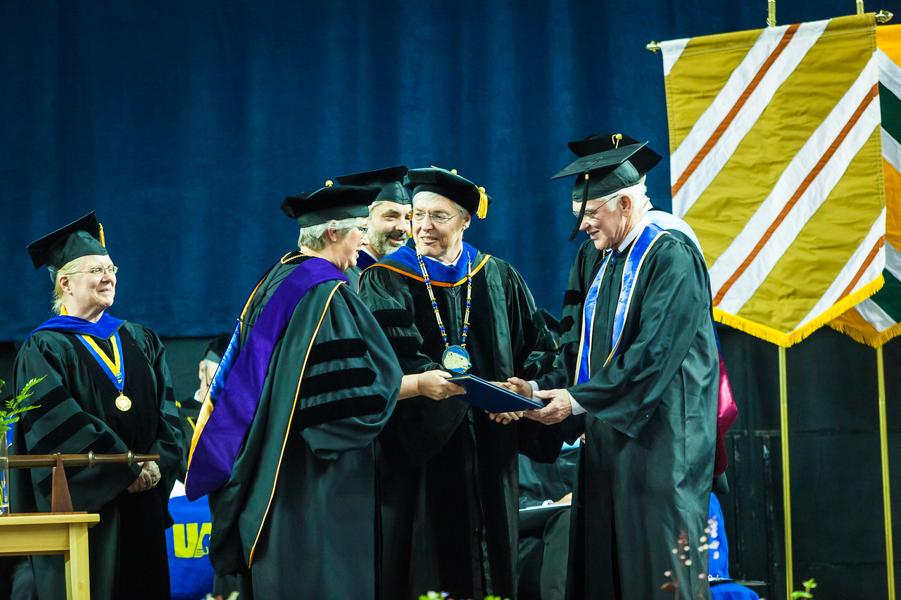 Col. Bill Brophy, USA, retired, receives the Meritorious Service Award at the commencement ceremony May 6, 2017, at the Carlson Center.