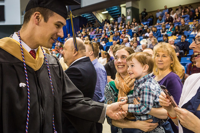 Master of Business Administration graduate Phil Hokenson greets wife Laura, bachelor of arts graduate in social work, and their 2-year-old son, Max, at the 2017 commencement ceremony.