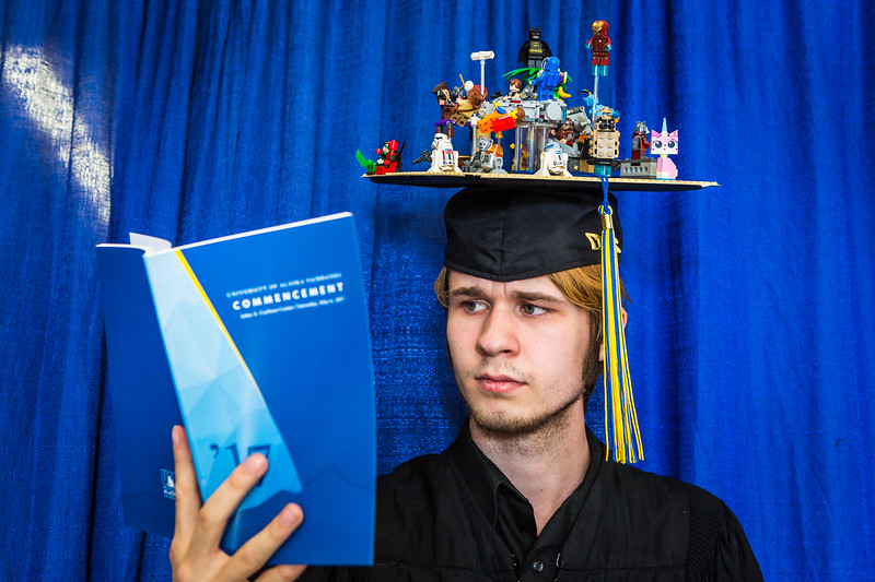 Wearing an ornate cap made with miniature Lego figurines, Ryan Osborne poses for a photograph before the start of the 2017 commencement ceremony, Saturday, May 6, at the Carlson Center.