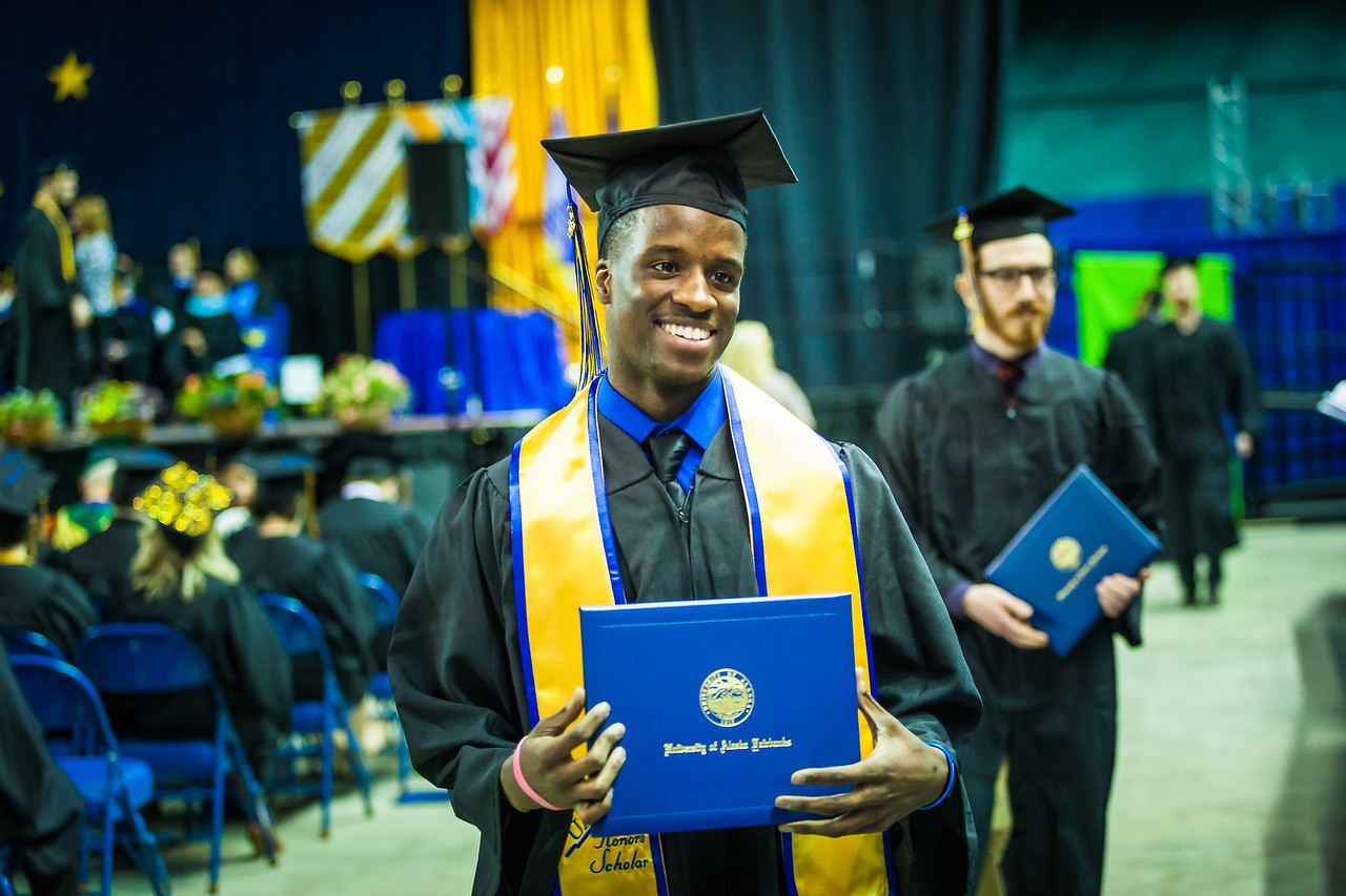 Farimang Touray Jr. is all smiles as he poses for his family's cameras during the 2017 commencement ceremony at the Carlson Center Saturday, May 6.