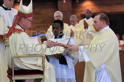 Deacon Chris Moran receives the Book of Gospels from Bishop Malooly during the Ordination of eight Deacons at The Church of the Holy Child, Saturday, August 19, 2017. wwwDonBlakePhotography.com