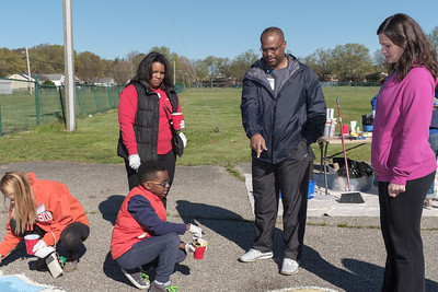 Richmond Public School's Superintendent instructs volunteer Michael Hill on how to paint the map on the playground at Woodville Elementary School with the Junior League of Richmond
