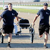 "Don Knight | The Herald Bulletin<br /> From left, APD's Zane Sparks and Matt Guthrie pull driver Sam Widger across the finish line to win the Sulky Race during the ""Guns & Hoses"" event at Hoosier Park on Saturday. The event is a fundraiser for the Madison County Fire Rescue House."
