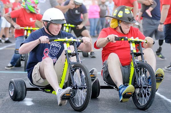 "Don Knight | The Herald Bulletin<br /> From left, Chesterfield Police Chief Billy Ingles and AFD's Mark Keck compete in the second leg of the Tricycle Race during the ""Guns & Hoses"" event at Hoosier Park on Saturday. The event is a fundraiser for the Madison County Fire Rescue House."