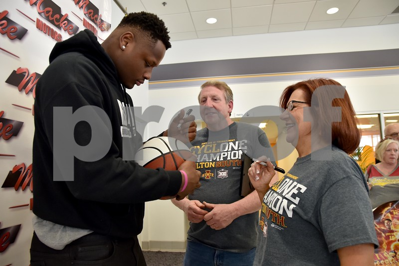 -Messenger photo by Britt Kudla<br /> Iowa State Monte Morris signs a basketball for Teresa and Phil Hood of Clarion during meet-N-greet on Friday at Mack Motors