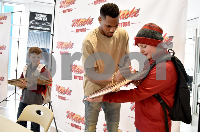 -Messenger photo by Britt Kudla<br /> Iowa State Monte Morris signs a Cyclones plaque for Caleb Blair (12 year old) during a meet-N-greet on Friday at Macke Motors
