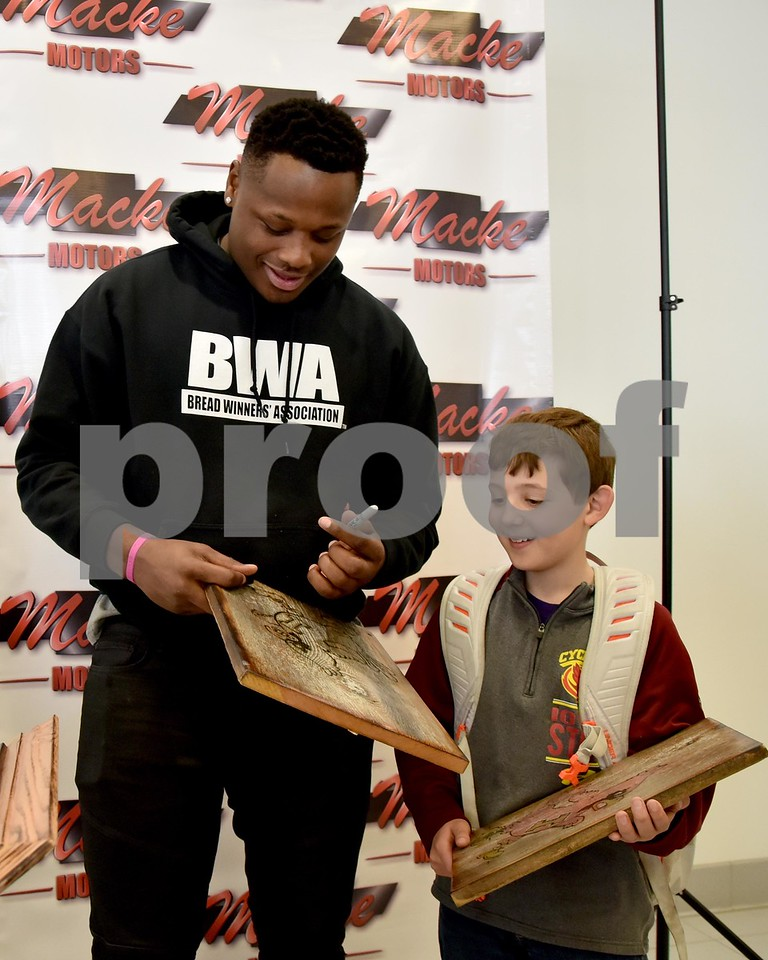 -Messenger photo by Britt Kudla<br /> Iowa State Monte Morris autographs Tristan Blair (11 year old) Cyclones plaque during a meet-N-greet on Friday at Macke Motors