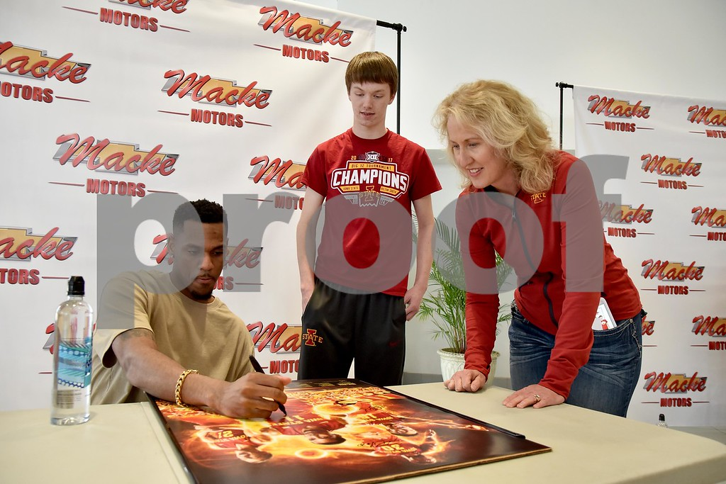 -Messenger photo by Britt Kudla<br /> Iowa State Monte Morris autograph a poster for Kay Crabb (right) and Connor Crabb of Sac City during a meet-N-greet on Friday at Macke Motors