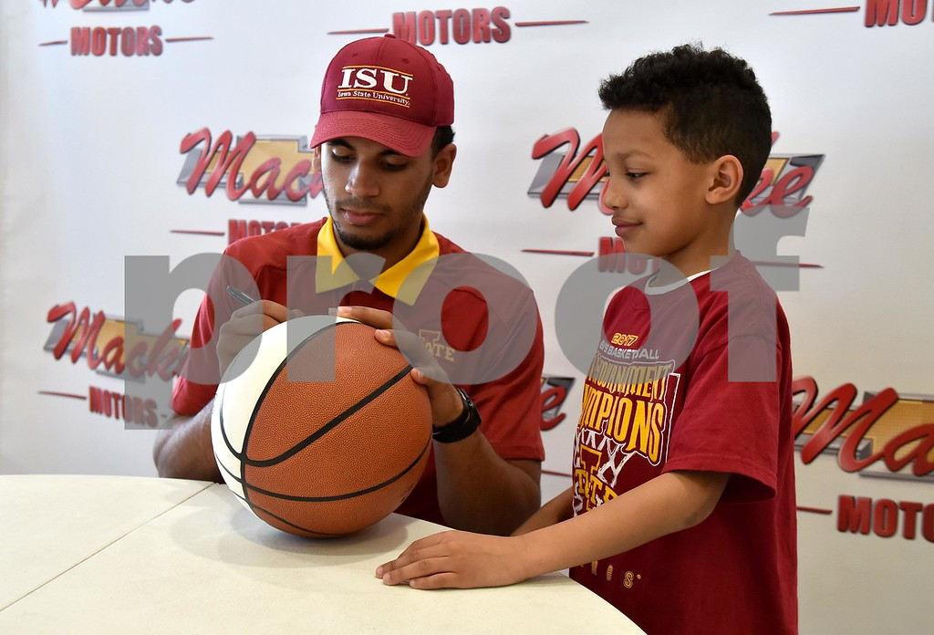 -Messenger photo by Britt Kudla<br /> Iowa State Nazareth Mitrou-Long autograph a basketball for Tayven Wilson (8) of Jefferson during a meet-N-greet on Friday at Macke Motors