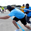 John P. Cleary |  The Herald Bulletin<br /> Members of the Nachos and Hogwash men's team, foreground, stretch toward the finish line trying to catch their opponent in the Human Truck Pull Saturday.<br /> They finished 2nd in the men's division.
