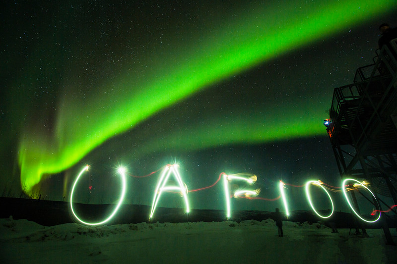 "While waiting for rocket launches at the Poker Flat Research Range on Feb. 16, spectators paint ""UAF 100"" with light during a stunning aurora display. This year is UAF's centennial."