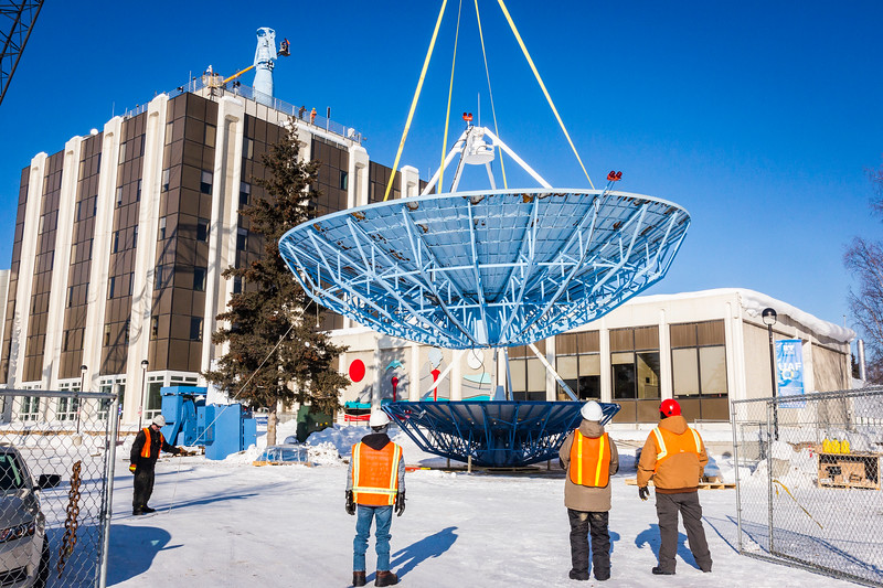 A crane lowers the old 10-meter antenna from the roof of the Elvey Building on Thursday, March 16, 2017, ending the dish's 25 years of service to the Geophysical Institute on the Fairbanks campus. A new 9-meter antenna will replace the retired dish and continue to retrieve scientific data from polar-orbiting satellites.