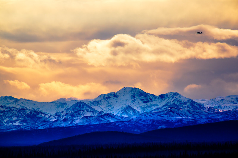 A propeller plane flies over the Alaska range in late October.