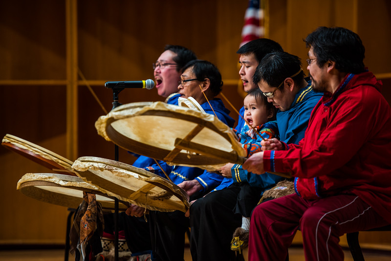 Performers play drums on the stage of the Davis Conert Hall as a part of the Festival of Native Arts.
