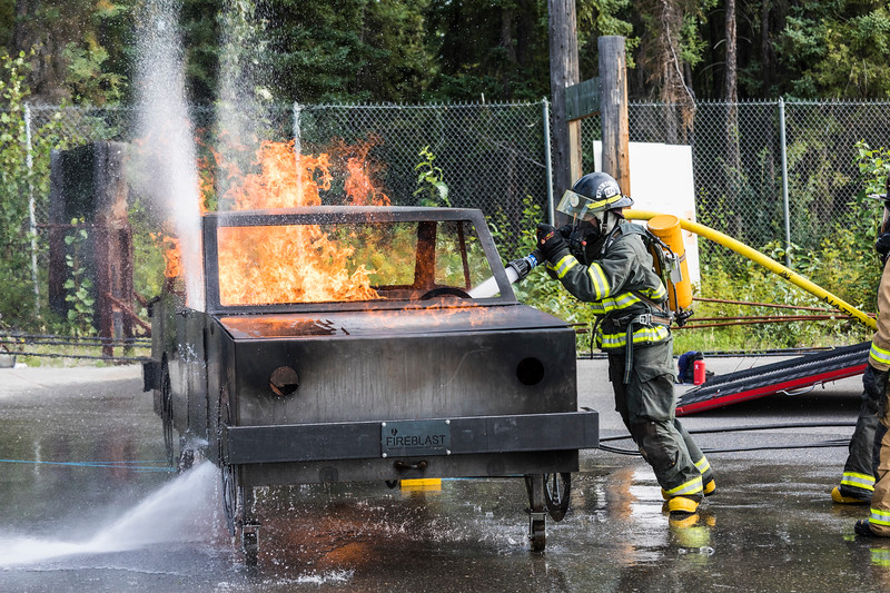 A participant in UAF Community and Technical College's 2017 Summer Fire Academy practices on a simulated car fire at the Fairbanks Regional Fire Training Center on Monday, July 31, 2017.