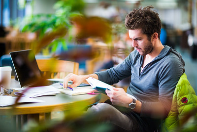 Jordy Bernard poses for a portrait in the Rasmusson Library while studying.