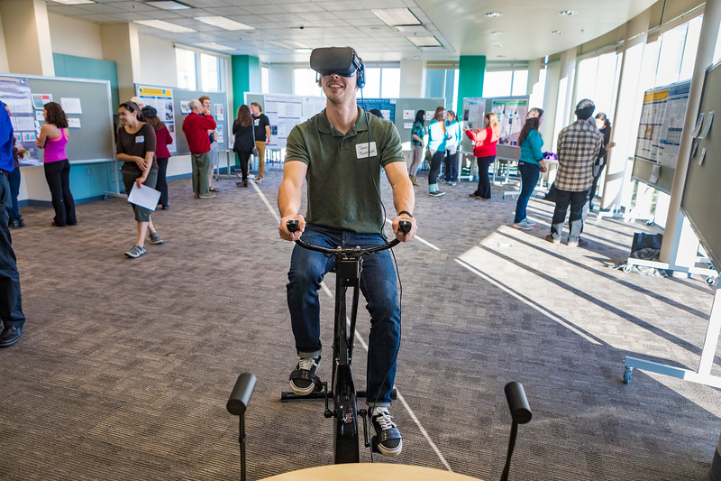 School of Management student Jesse Kaczmarski demonstrates his research using virtual reality during an event hosted by the Biomedical Learning and Student Training program at the IARC building on campus.
