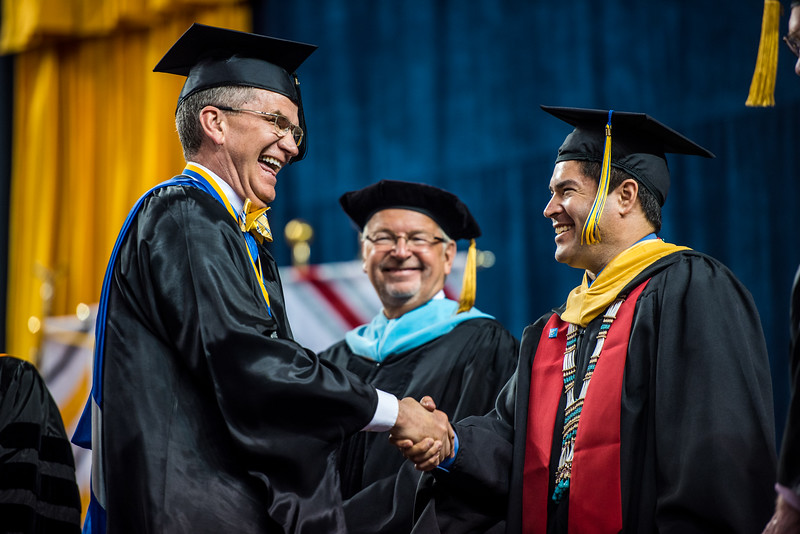 Greg Owens (left), Associate Professor of Mathematics and Developmental Education, Emeritus, shakes hands with Vice Chancellor of Rural Community and Native Education Evon Peters (right) at UAF's Commencement 2017.