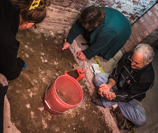 Community volunteers take their turn digging and sifting through the crypt underground at Old North Church