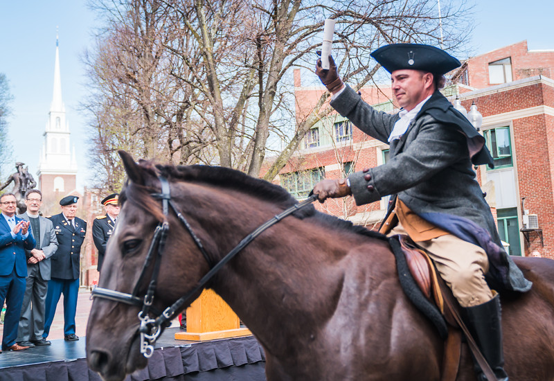 Holding his order, Paul Revere rides down Hanover Street on Brown Beauty
