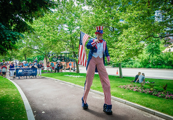 Uncle Sam on Stilts leads the crowd through Christopher Columbus Park