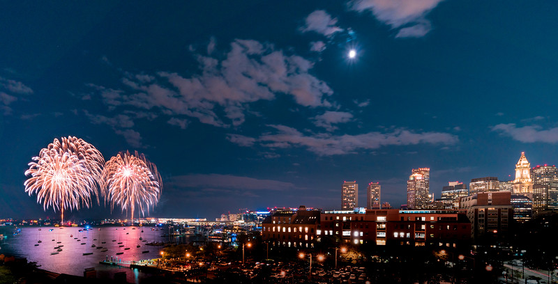 Streams of fireworks emerge from dueling barges in Boston Harbor