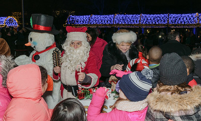 Santa, Frosty and FOCCP President Joanne Hayes Rines are joined by kids to flip the switch at the trellis lighting