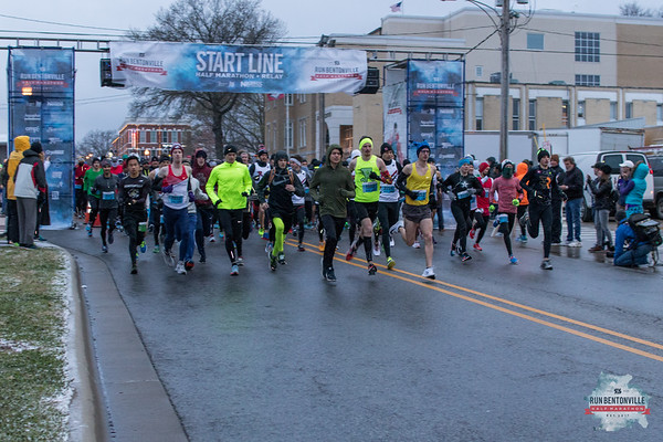 Runners for the Bentonville Half Marathon undaunted by the 20 degree temps, snow and 10-15 mph winds took off at the start line at the Bentonville Square.