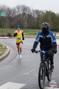 Bundled up to protect from the bitter cold Bentonville Half Marathon runners crossed mile 4 at the corner of Memorial Park.