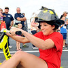John P. Cleary | The Herald Bulletin<br /> The eighth annual Guns & Hoses charity event at Hoosier Park. Morgan Williams, of Chesterfield Fire Department, peddles her way around the track during the Tricycle Race.