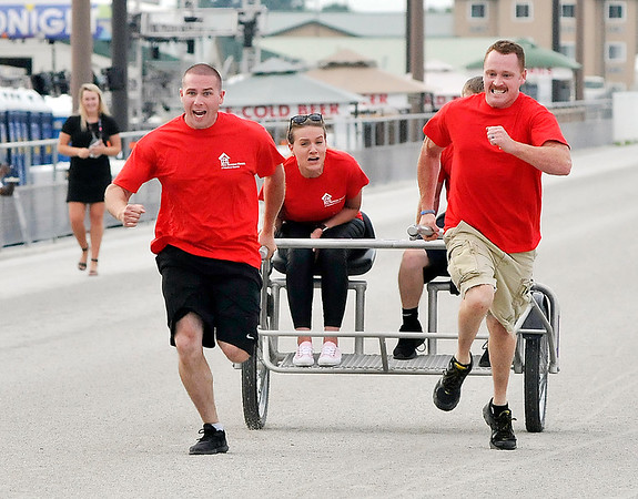 John P. Cleary   The Herald Bulletin<br /> The eighth annual Guns & Hoses charity event at Hoosier Park. Ryan Moore, of Elwood fire department, and Landin Henson, of Anderson fire department, pull the winning sulky and their riders during the First Responder Sulky Race.