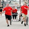 John P. Cleary | The Herald Bulletin<br /> The eighth annual Guns & Hoses charity event at Hoosier Park. Ryan Moore, of Elwood fire department, and Landin Henson, of Anderson fire department, pull the winning sulky and their riders during the First Responder Sulky Race.