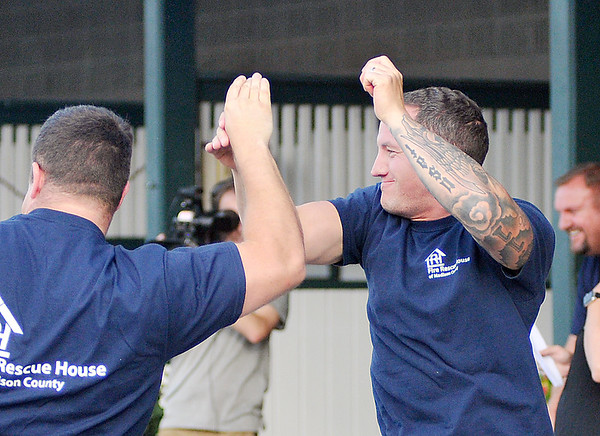 John P. Cleary   The Herald Bulletin<br /> The eighth annual Guns & Hoses charity event at Hoosier Park. Matt Guthrie, of APD, gets congratulation from a fellow officer after winning the Bounce Horse Race.