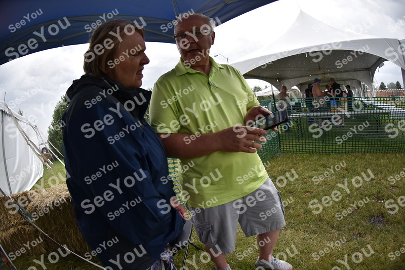 -Messenger photo by Britt Kudla <br /> Alicia (left) and Kevin Hunt taking cover during a rain storm while celebrating their 40th Wedding Anniversary during ZZ Top Concert on Saturday at Rogers Park