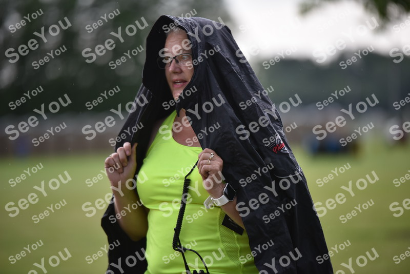 -Messenger photo by Britt Kudla<br /> Tammy Oester of Fort Dodge takes cover from the rain during ZZ Top concert on Saturday at Rogers Park