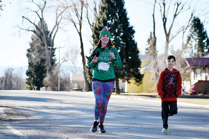 Matthew Gaston | The Sheridan Press<br>Laci Schwend and her son Bronson, 7, on the final leg of the Tongue River Valley Community Center's Ugly Sweater Run Saturday, Dec. 15, 2018.