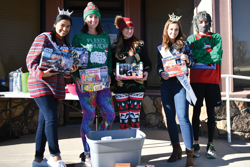 Matthew Gaston | The Sheridan Press<br>From left, Beck Bridger, Laci Schwend, Amber Miles, Taylor Greig and Jason Barron pose for a photo with some of the toys donated for the Tongue River Valley Community Center's Ugly Sweater Run Saturday, Dec. 15. 2018.