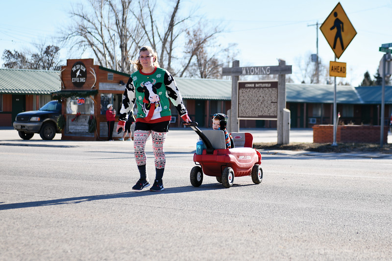 Matthew Gaston | The Sheridan Press<br>Dana Peirce nears the finish line of the Tongue River Valley Community Center's Ugly Sweater Run with 4-year-old Hayden Peirce in tow Saturday, Dec. 15, 2018.