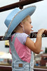 Nevaeh Savage, 4, from Morning Sun, peers through the fence eager for the start of the 10th Annual Wapello PRCA Rodeo Saturday, July 14, 2018.