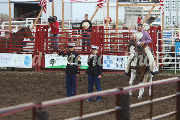 USMC Pvt. Elizabeth Chaney (center) sings the National Anthem as local USMC recruiting officer Staff Sgt. Miguel Gamboa salutes and rodeo announcer Kelly Kenney places his cowboy hat to his heart while saddled on Rio at the beginning of 10th Annual Wapello PRCA Rodeo Saturday, July 14, 2018.