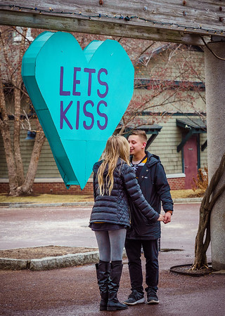 Young couple kisses under the Let's Kiss heart