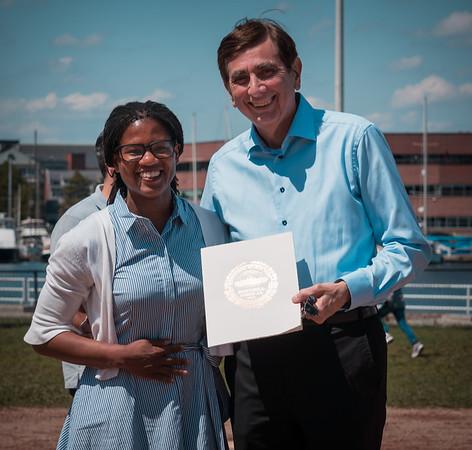 "Boston City Councilor Lydia Edwards presents a citation to Robert ""Ted"" Tomasone"