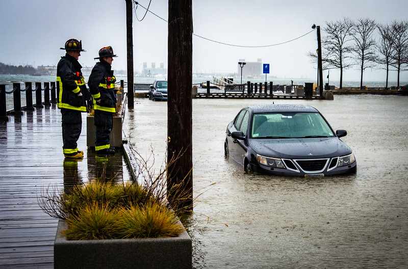 Firefighters investigate waterfront flooding during the storm surge at Sargent's Wharf on Boston's waterfront in March 2018