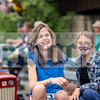 Rosalyn Tanner and sister Alex grin from their seat just behind a tractor.