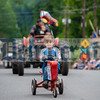A very serious Averill McCullough pedals Lee Hartwell's pedal tractor down the street.