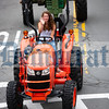 Emma Hess waves from behind the wheel of a Kubota.