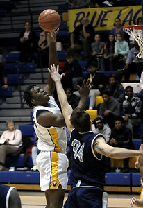 Photo by Matt Griffith/VU  Vincennes University's Chinedu Okanu, left, puts up a shot over Kaskaskia's Jacob Thompson, 34, Wednesday night in the P.E. Complex.
