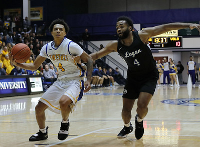 Photo by Matt Griffith/VU  Vincennes University's Craig Porter, left, picks up his dribble on a drive to the basket as he breaks free from John A. Logan's Mark Lancaster Saturday night in the P.E. Complex.