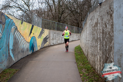 "Runners gathered at the Bentonville Square for a ""short"" 5k or 13.1 mile run throughout the streets of Bentonville, concluding with the dreaded Crystal Bridges Hill. Around mile 10, after passing the dog park, runners followed the Razorback Greenway toward Slaughter Pen."
