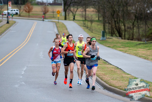 "Runners gathered at the Bentonville Square for a ""short"" 5k or 13.1 mile run throughout the streets of Bentonville, concluding with the dreaded Crystal Bridges Hill. At miles 3-4 they ran through Memorial Park."
